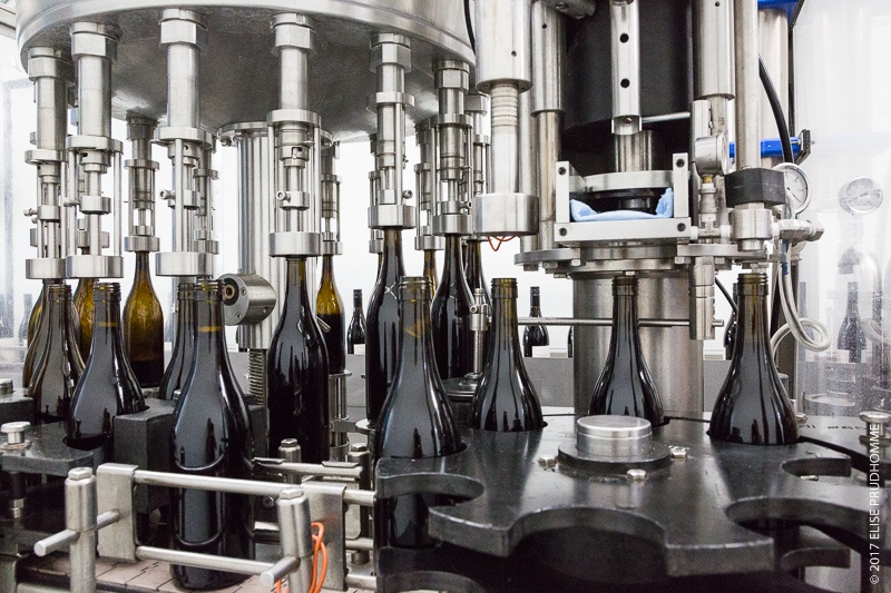Three Feather bottles enter the StelvinLux screwcapping machine