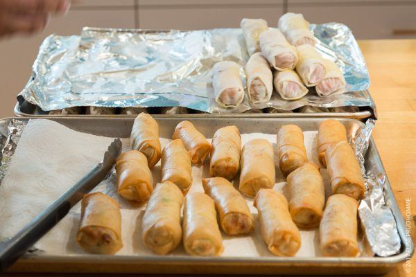 Cooked spring rools (foreground) and uncooked spring rolls (background)