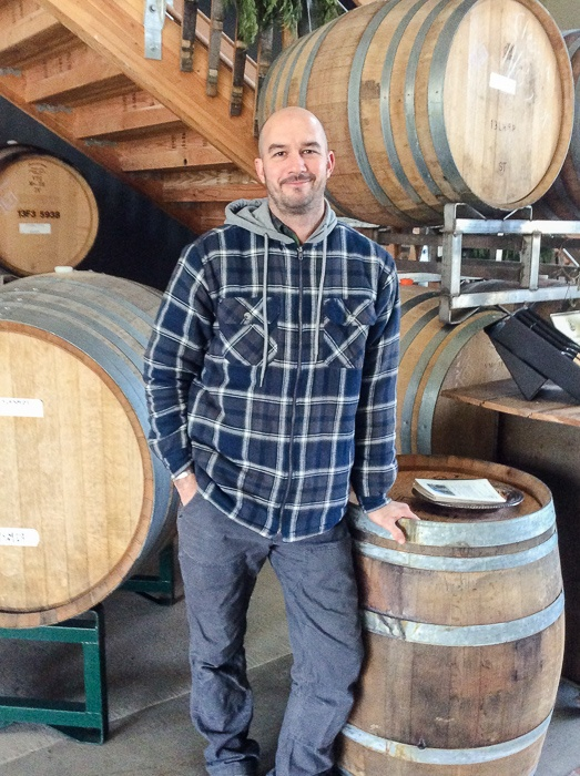 Dan Duryee, winemaker, stands amongst oak barrels at Lady Hill Winery tasting room in Saint Paul, Oregon.