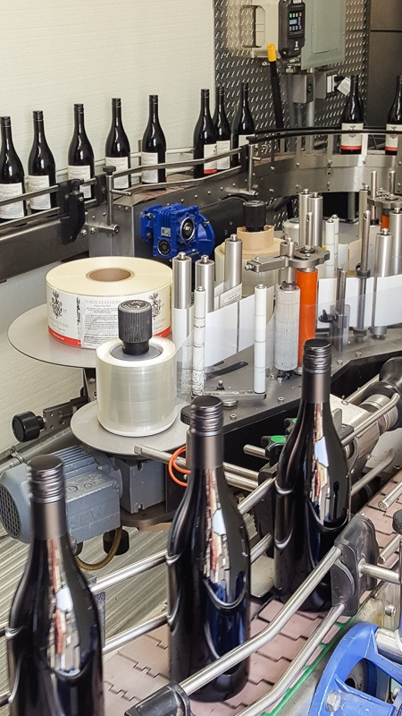 Three Feather bottles leave the StelvinLux screwcapping machine on the assembly line-up by Signature Bottlers.