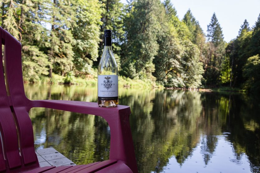 A bottle of Three Feathers Blanc de Noirs at the lake in Oregon summer 2019