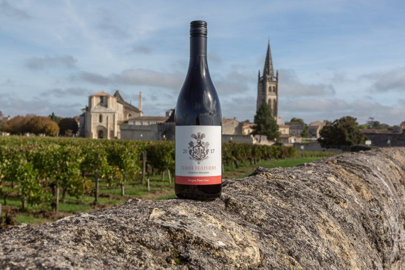 A bottle of Three Feathers Estate Pinot Noir perched on a vineyard wall with the town Saint-Emilion in the background, Bordeaux region, Gironde, France.