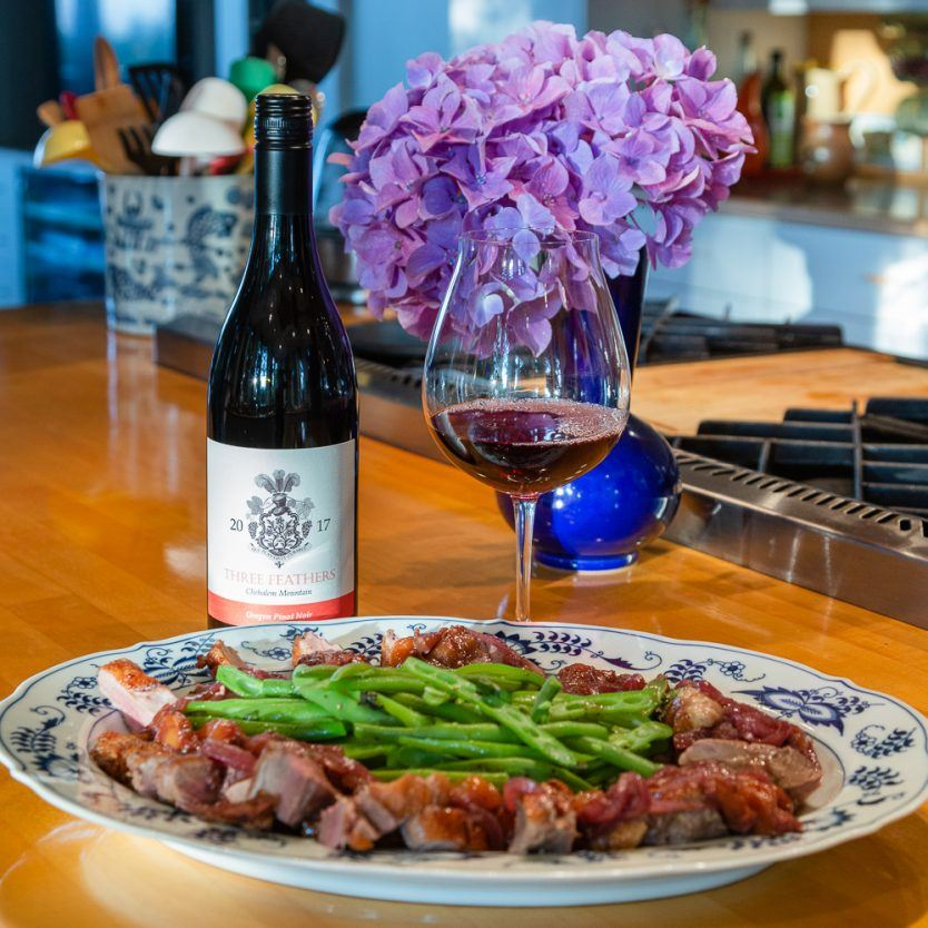 Presentation of a seared duck breast recipe with cherry Pinot Noir sauce and french-cut green beans