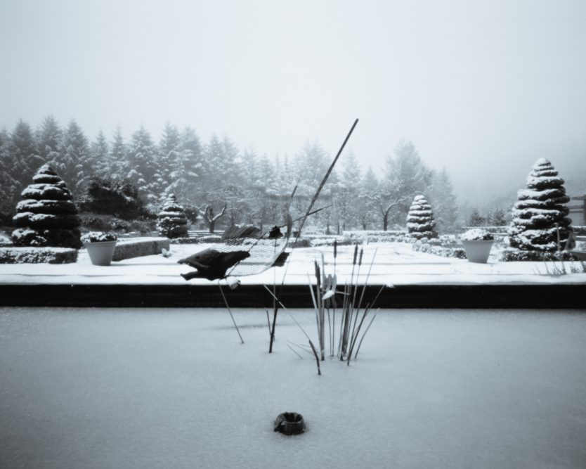 Black and white pinhole photograph of snow-ladden formal gardens at Three Feathers Estate.